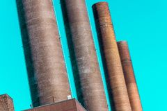 Immagine deliberatamente curvata dell'estratto dei camini della centrale elettrica di grande impianto industriale fotografie stock