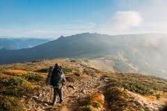 Immagine dell'alpinista del giovane che sta in cima alla roccia Fotografie Stock