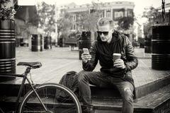 Immagine dell'uomo che mangia caffè e che per mezzo dello smartphone Immagini Stock Libere da Diritti
