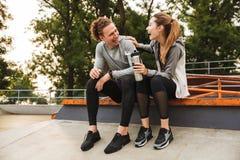 Immagine dell'uomo delle coppie e della donna sportivi felici 20s in tute sportive, La immagini stock