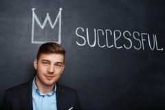 Immagine dell'uomo sopra la lavagna con la corona ed il testo riusciti immagini stock