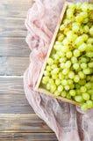Immagine dell'uva verde in scatola di legno, sul panno Fotografia Stock