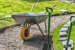 Immagine della carriola nel cortile con erba verde Fotografia Stock