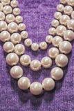 Immagine della collana della perla sul vestito porpora Fotografia Stock