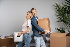 Immagine della condizione dell'uomo e della giovane donna fra le scatole di cartone immagini stock libere da diritti