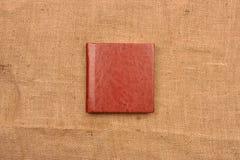 Immagine della copertura di cuoio bruno-rossastro dell'album di foto sul backg della iuta Fotografia Stock Libera da Diritti