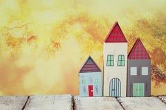 Immagine della decorazione variopinta di legno d'annata delle case sulla tavola di legno davanti a fondo vago Immagine Stock Libera da Diritti