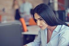 Immagine della donna che per mezzo del computer portatile mentre sedendosi al suo scrittorio Immagini Stock