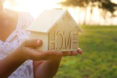 Immagine della donna che tiene piccola casa di legno all'aperto alla luce di tramonto immagini stock
