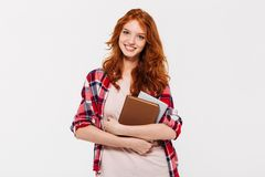 Immagine della donna sorridente dello zenzero in camicia che abbraccia i libri Fotografia Stock Libera da Diritti