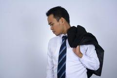 Immagine della foto di giovane uomo d'affari asiatico che tiene il suo rivestimento del vestito sulla sua spalla isolata su bianc Fotografie Stock Libere da Diritti
