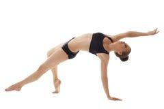 Immagine della ginnasta femminile sveglia che pratica nello studio Immagini Stock