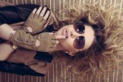Immagine della giovane donna calda di fascino della ragazza alla moda con i guanti di vetro che si trovano sulle armi attrave Fotografie Stock