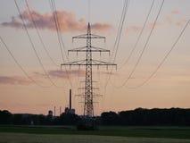 Immagine della linea elettrica durante il tramonto con la centrale elettrica fotografia stock