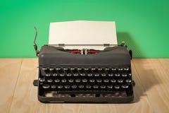 Immagine della macchina da scrivere d'annata sulla carta da parati verde Immagine Stock