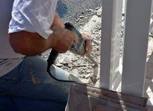 Immagine della macchina del trapano della piastrella di ceramica della tenuta del lavoratore dell'uomo mentre perforando le vecch Fotografia Stock