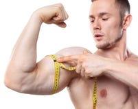 Immagine della misura muscolare dell'uomo il suo bicipite con nastro adesivo di misurazione nei centimetri isolato su backgound b Immagine Stock