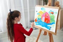 Immagine della pittura del piccolo bambino facendo uso del cavalletto immagini stock libere da diritti