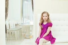 Immagine della ragazza sveglia sorridente in vestito porpora astuto immagini stock libere da diritti
