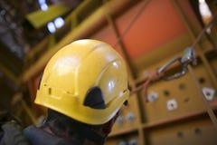 Immagine della testa del lavoratore di accesso della corda che indossa un casco di sicurezza giallo di protezione di caduta mentr fotografia stock