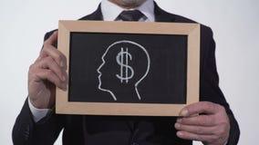 Immagine della testa di simbolo del dollaro sulla lavagna in mani dell'uomo d'affari, ingordigia per soldi archivi video