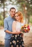 Immagine delle coppie adorabili e sorridenti, fra i pini fotografia stock libera da diritti