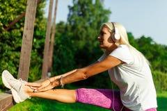 Immagine delle cuffie d'uso della donna sportiva sull'allungamento Immagine Stock Libera da Diritti