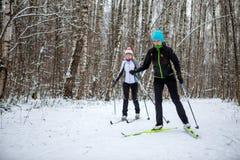 Immagine delle donne e degli uomini di sport che sciano nella foresta di inverno Immagini Stock Libere da Diritti