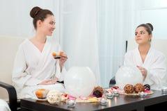 Immagine delle ragazze adorabili che bevono tè nel salone di bellezza Immagine Stock Libera da Diritti