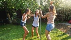 Immagine delle ragazze di risata allegre in vestiti bagnati che ballano nel giardino e che tengono il tubo flessibile dell'acqua  fotografia stock libera da diritti