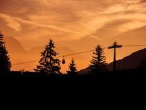 Immagine delle siluette dell'ascensore e degli alberi di sci durante l'alba nel primo mattino immagini stock