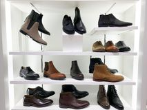 Immagine dello scaffale di negozio con le scarpe del ` s degli uomini Immagini Stock