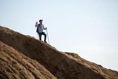 Immagine dello sportivo con lo zaino e dei bastoni da passeggio sulla collina fotografia stock libera da diritti