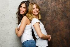 Immagine di bella donna castana e bionda che sta l'un l'altro con le loro parti posteriori Fotografie Stock