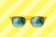 Immagine di concetto di estate: occhiali da sole gialli con le riflessioni della palma isolati nel fondo a strisce giallo pastell Immagine Stock Libera da Diritti