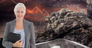 Immagine di Digital del diario della tenuta della donna di affari mentre stando sulla strada contro la roccia ed i grafici Fotografia Stock