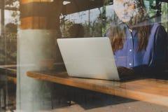 Immagine di facendo uso di/che scrive delle mani della donna sul fuoco selezionato per ordinatori del computer portatile sulla ta immagini stock libere da diritti