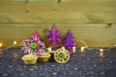 Immagine di fotografia dell'alimento di Natale con alimento tradizionale dei mince pie con il fiore inglese di inverno e le luci  Fotografia Stock