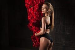 Immagine di giovane atleta femminile muscolare che indossa usura nera di sport che sta vicino ai grandi fiori su fondo scuro Cult fotografia stock