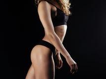 Immagine di giovane parte posteriore dell'atleta femminile su fondo scuro Posa di modello di forma fisica nello studio Immagini Stock Libere da Diritti