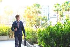 Immagine di giovane uomo di affari che cammina in avanti con una cartella immagine stock libera da diritti