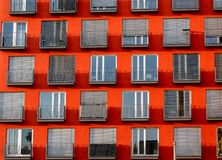 Immagine di grattacielo rosso con le finestre e balconi e ciechi fotografia stock libera da diritti