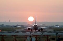 Immagine di Iconical di atterraggio di aeroplano ad un aeroporto al tramonto immagini stock libere da diritti
