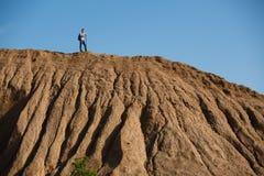 Immagine di lontano del turista maschio con i bastoni per la camminata sulla collina contro il cielo blu Immagini Stock