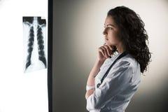 Immagine di medico attraente della donna che esamina raggi x immagine stock libera da diritti