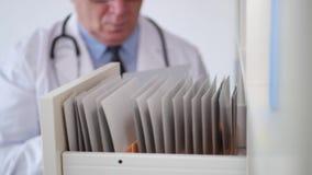 Immagine di medico che cerca nei documenti dell'archivio dell'ospedale e nelle cartelle sanitarie video d archivio