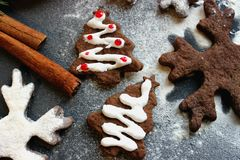 Immagine di Natale Alberi di Natale e fiocchi di neve del pan di zenzero del cioccolato spruzzati con farina su un fondo scuro Immagine Stock