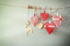 Immagine di Natale dei cuori e dell'albero rossi del tessuto luci di legno della ghirlanda e della renna, appendenti sulla corda Fotografia Stock