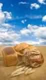 Immagine di pane e di grano contro il primo piano del cielo fotografia stock