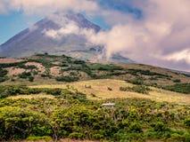 Immagine di piccola casa sotto la grande montagna del pico immagini stock